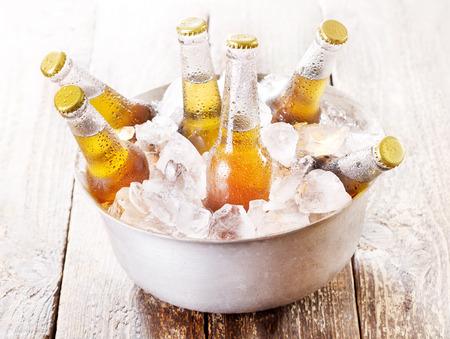 cerveza: botellas frías de cerveza en un cubo con hielo en mesa de madera Foto de archivo