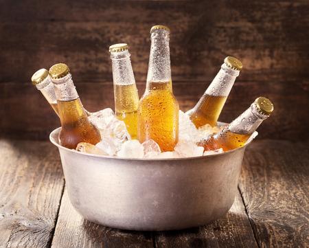 bebidas frias: botellas frías de cerveza en un cubo con hielo en mesa de madera Foto de archivo