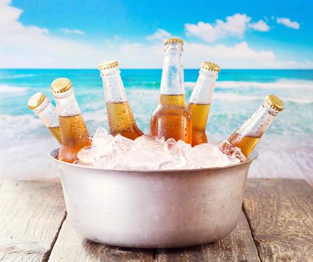 cubos de hielo: botellas frías de cerveza en un cubo con hielo sobre el mar Foto de archivo