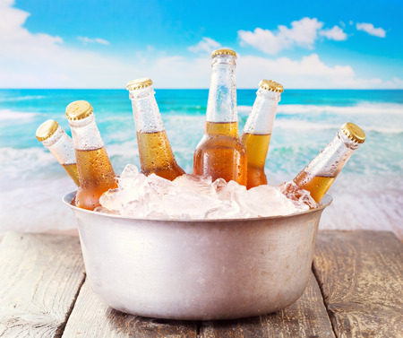 drink at the beach: cold bottles of beer in bucket with ice over sea