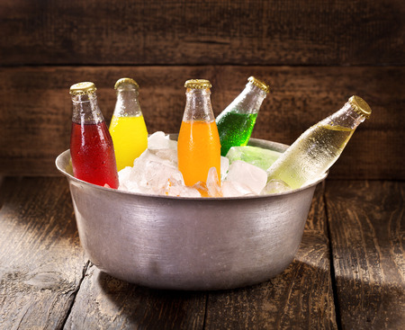 various bottles of soda in the bucket with ice on wooden table Foto de archivo