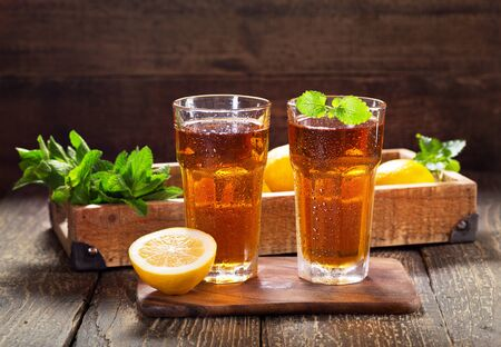 glasses of ice tea with mint and lemon on wooden table 写真素材