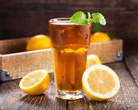 herb tea: glass of ice tea with mint and lemon on wooden table