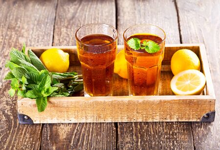 ice tea: glasses of ice tea with mint and lemon on wooden table Stock Photo