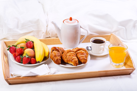 trays: Breakfast in bed. Tray with coffee, croissants and fruits