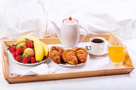 Ontbijt op bed. Lade met koffie, croissants en fruit Stockfoto