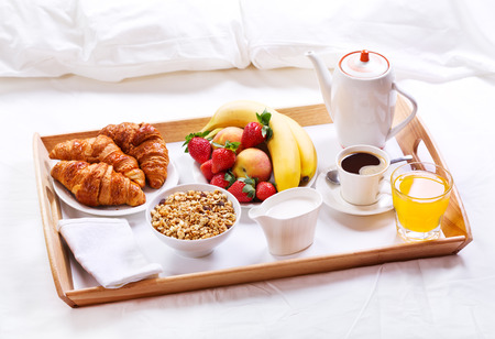 luxury hotel room: breakfast in bed. Tray with coffee, croissants, cereals and fruits