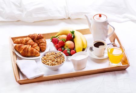 Desayunar en la cama. Bandeja con café, croissants, cereales y frutas Foto de archivo - 40979480