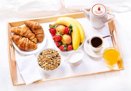 침대에서 아침 식사. 커피, 크로와상, 시리얼과 과일 트레이