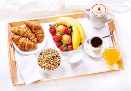 continental breakfast: Breakfast in bed. Tray with coffee, croissants, cereals and fruits
