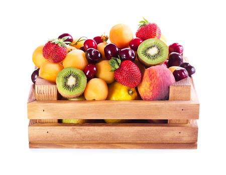 verse verschillende vruchten in houten kist op witte achtergrond