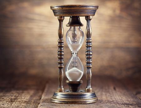 reloj de arena: antiguo reloj de arena en el fondo de madera