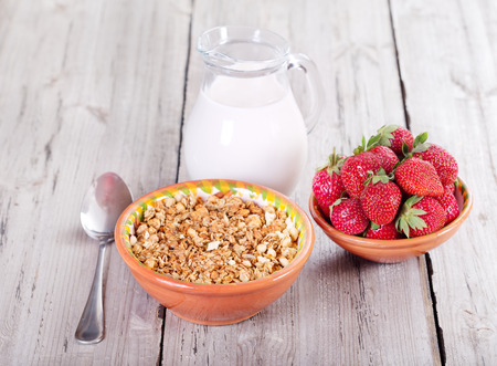 cereales: breakfast with cereals, milk and strawberries on wooden table Foto de archivo