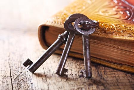 나무 테이블에 오래 된 책을 가진 오래 된 키