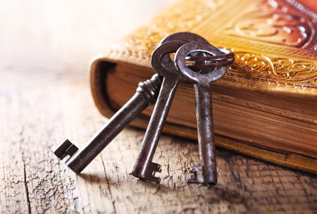 old keys with old book on wooden table