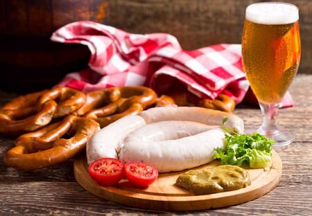 veal sausage: bavarian white sausages with pretzel and glass of beer on wooden table Stock Photo