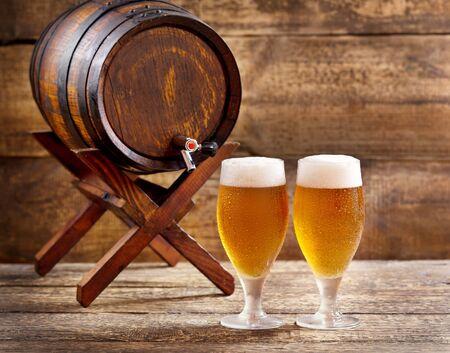 barrels: glasses of beer with barrel on wooden background