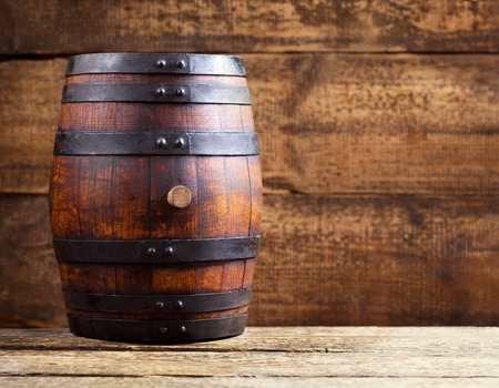 still life of wine: old wooden barrel on rustic wooden background