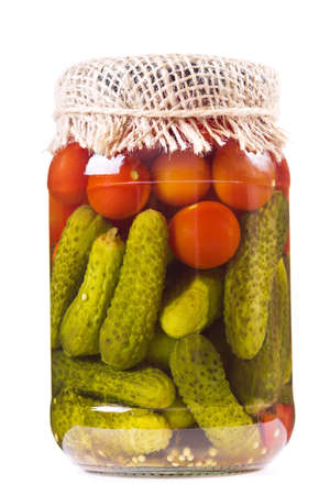 marinated gherkins: canned tomatoes and pickled cucumbers in glass jar on white background