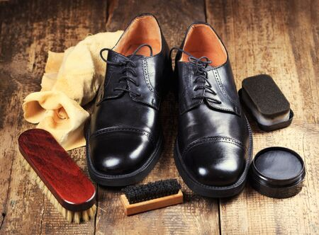 shine: black  shoes with care accessories on a wooden background