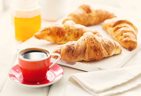 fresh morning: breakfast with croissants and coffee on wooden table