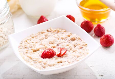 bowl of porridge with strawberry on wooden table