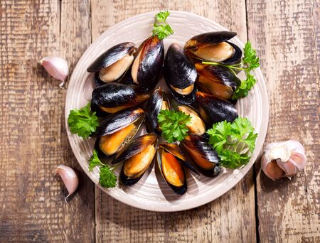 shellfish: plate of mussels with parsley on wooden table