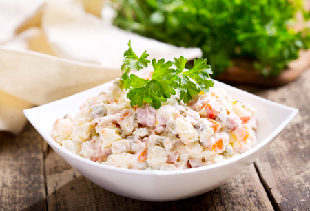vegetable salad: bowl of traditional russian salad on wooden table