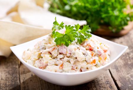 kom van traditionele Russische salade op houten tafel