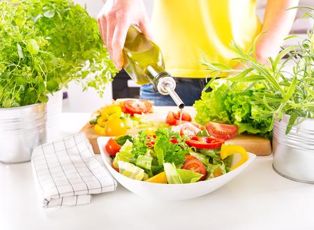 ensalada verde: manos de una mujer que vierte el aceite de la botella en el plato de ensalada en la cocina Foto de archivo