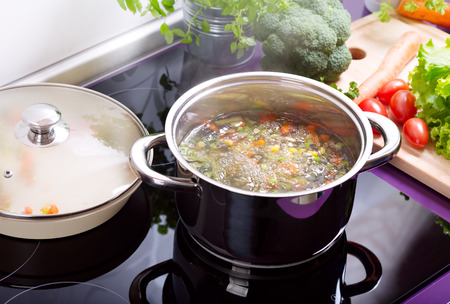 pan of vegetable soup in the cooker in the kitchen Standard-Bild