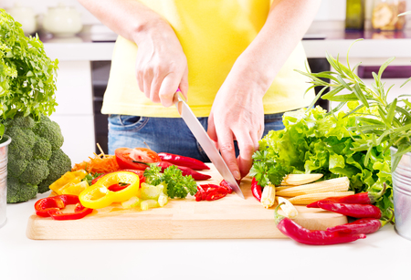 preparation: Female hands preparing vegetable salad on wooden board in the kitchen Stock Photo