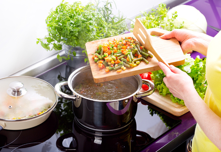 Vrouwelijke handen koken groentesoep in de keuken Stockfoto