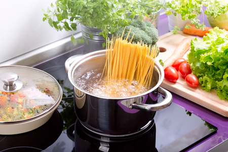 boiling: pan of boiling water with spaghetti on the cooker in the kitchen