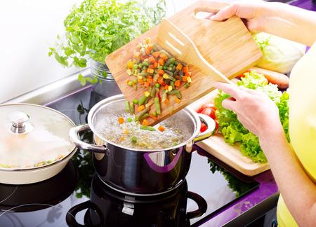 vrouwelijke handen groentesoep koken in de keuken