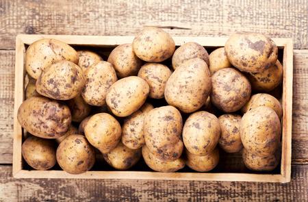 papas: patatas crudas en la caja de madera