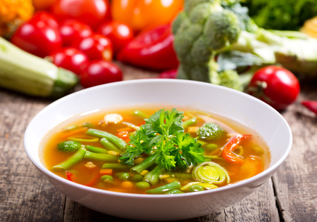 vegetable soup: bowl of vegetable soup on wooden table Stock Photo