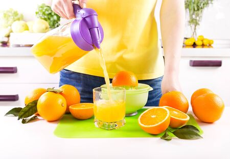 orange juice: woman pouring orange juice into glass in a kitchen
