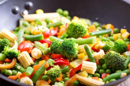 revuelva verduras fritas en la sartén Foto de archivo