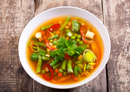 green bean: bowl of vegetable soup on wooden table Stock Photo