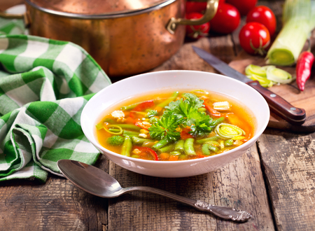 minestrone: bowl of vegetable soup on wooden table Stock Photo