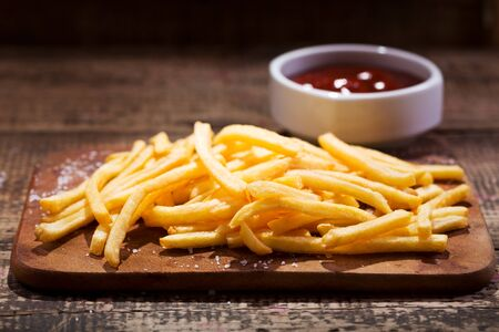fried potatoes with sauce on wooden table Foto de archivo