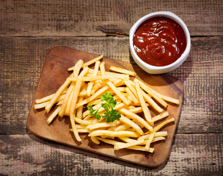 fried foods: fried potatoes with sauce on wooden table Stock Photo