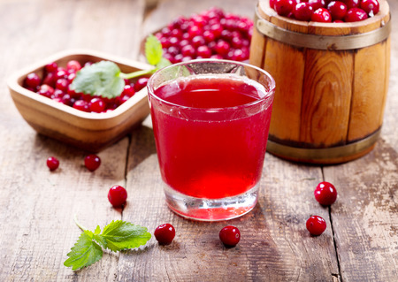 cranberries: glass of cranberry juice with fresh berries on wooden table