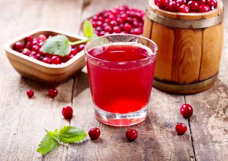 arandanos rojos: vaso de jugo de arándanos con bayas frescas en la mesa de madera Foto de archivo