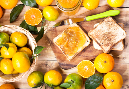 pain: toast with orange mandarin marmalade with fresh fruits on wooden table