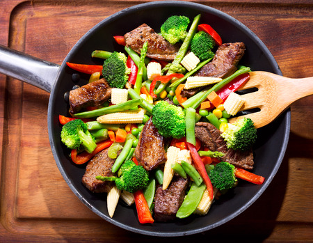 stir fried: meat with vegetable in a pan on wooden board