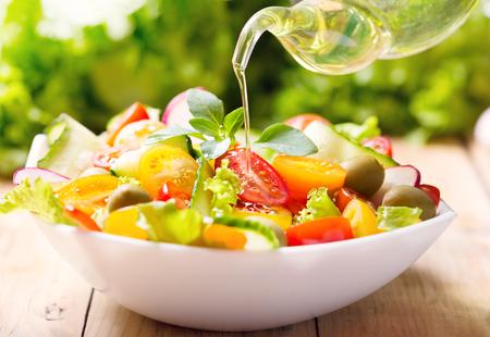Olivenöl in Schüssel Gemüsegemüse gießen