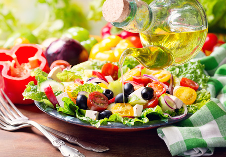 olive oil pouring into plate of fresh greek salad