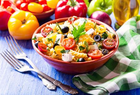 木製テーブルの上の野菜とパスタのサラダ ボウル 写真素材